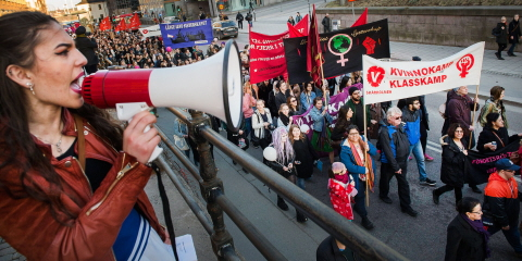 Demonstrators with banners marching on a road. In the forefront stands a woman with a megaphone.