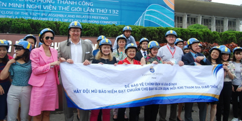 The members of the Riksdag delegation stand alongside each other with blue and yellow helmets on their heads. Some of them are holding a large banner. The banner contains two lines of Vietnamese text.