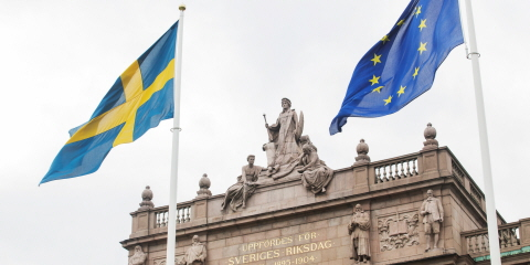 The Swedish flag and the EU flag outside the Riksdag.