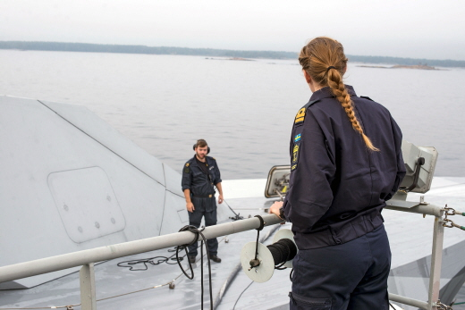 A male and a female soldier talking on the deck of a boat.