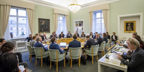 Members of The Committee on Foreign Affairs sitting at a table in an assembly room in the Riksdag.