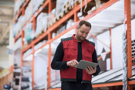 A male employee in a warehouse checks his touch pad.