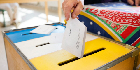 A close-up of a person's hand putting a ballot paper in the yellow ballot box.